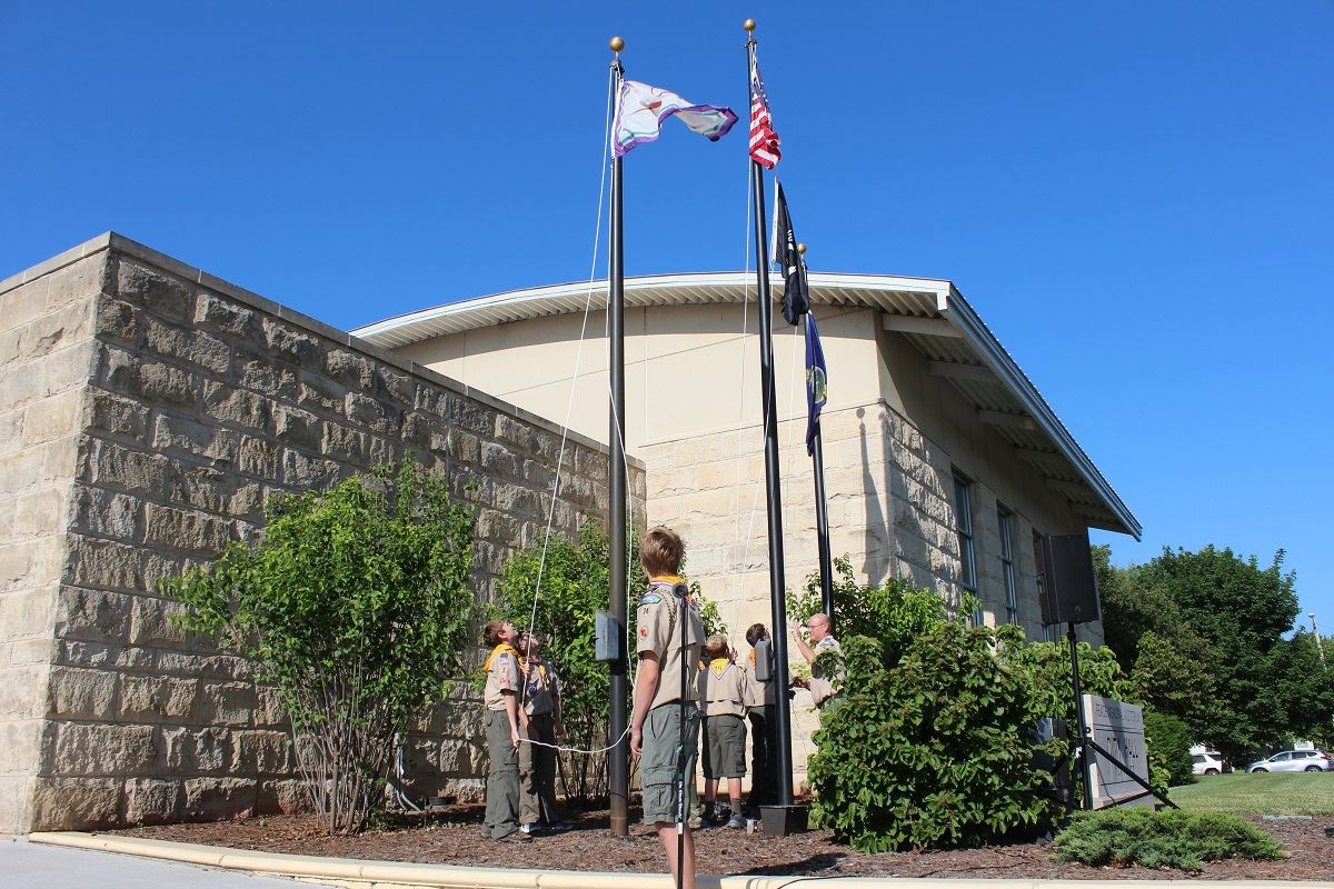 photo of boy scouts raising flags in front of City Hall